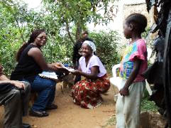 Project Manager, Rebecca Machiya, delivers a loan check to a sponsored mother
